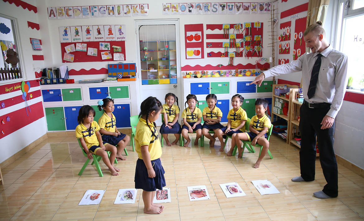 A foreign teacher teaching and instructing young children at a Kindergarten in China.