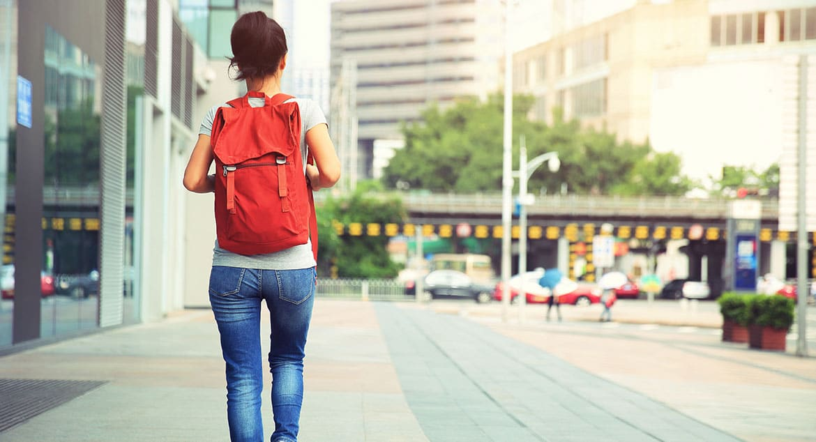 A girl with a red backpack walks away into the distance